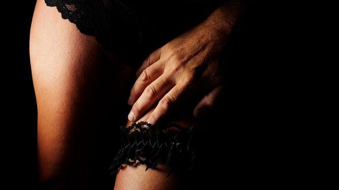 黒の下着を身に着けた女性の足に男性の手