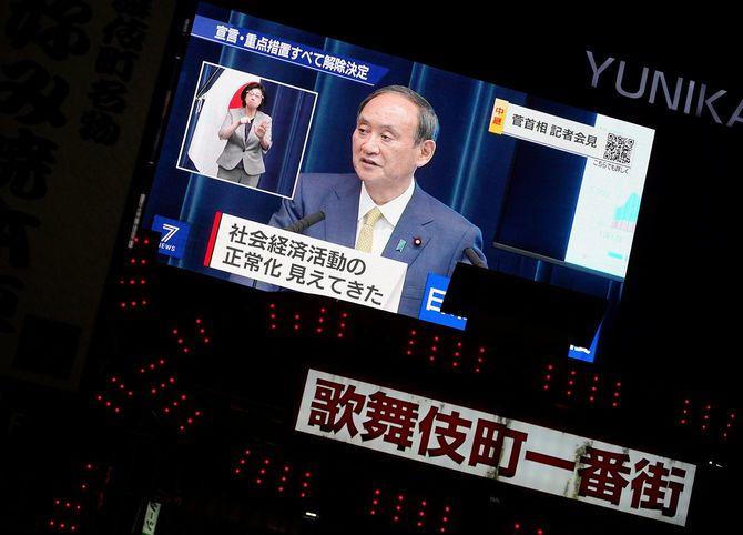 菅義偉首相の記者会見を映す大型ビジョン。政府は、新型コロナウイルス対策で半年近くに及んだ緊急事態宣言を30日の期限をもって全面解除すると発表した