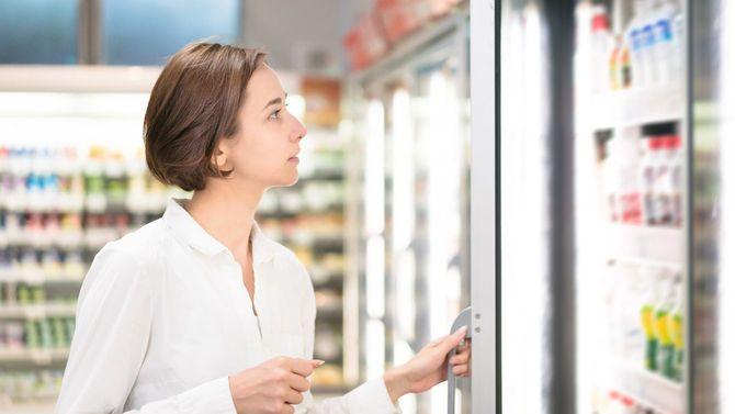スーパーで冷蔵庫の扉を開ける女性