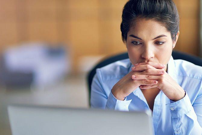 パソコン画面を見ながら考えている女性