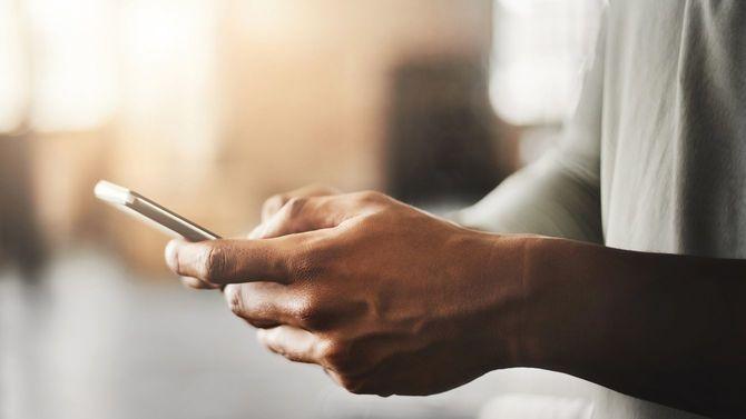 ジムでスマートフォンを使用している男性の手元