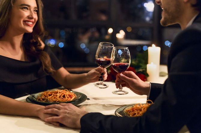 レストランでロマンティックなディナーをとる幸せなカップル