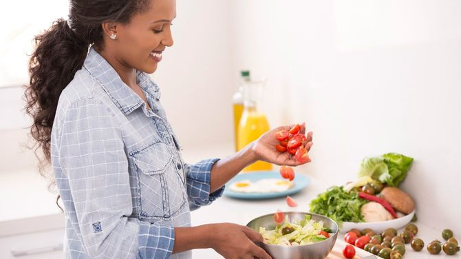 新鮮なサラダにチェリートマトを追加する女性