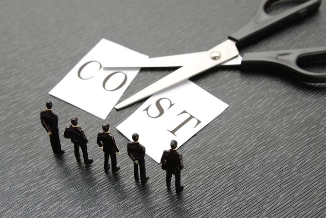 ハサミで切られたCOSTの紙を見ているビジネスマン模型