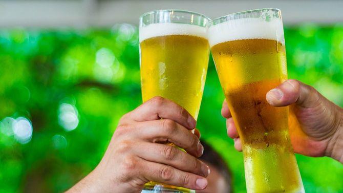 手にビールを持ち、乾杯するふたりの手元