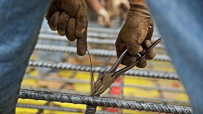 建設現場で鉄筋にワイヤーカッターをつけてワイヤーを結ぶ作業をしている作業員の手元