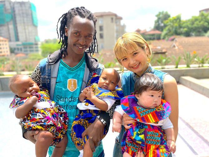 ラハ・ケニアの洋服を着た娘を抱く河野リエさん(右)。隣は創業時から同社に製品を提供するテーラーのウィリアムさんとその子どもたち