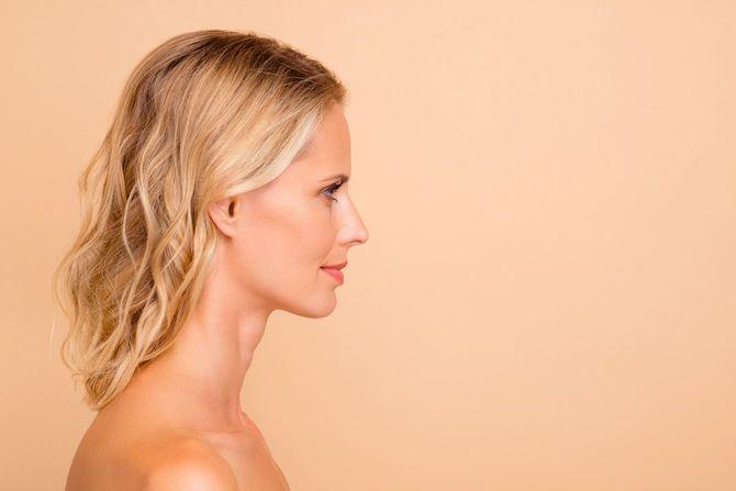 ボトックスコラーゲンデトックス広告コンセプト。プロフィールサイドビュー彼女の彼女の魅力的な波状髪の女性の肖像画ベージュの背景の上に孤立した純粋で明確なクリーンで完璧
