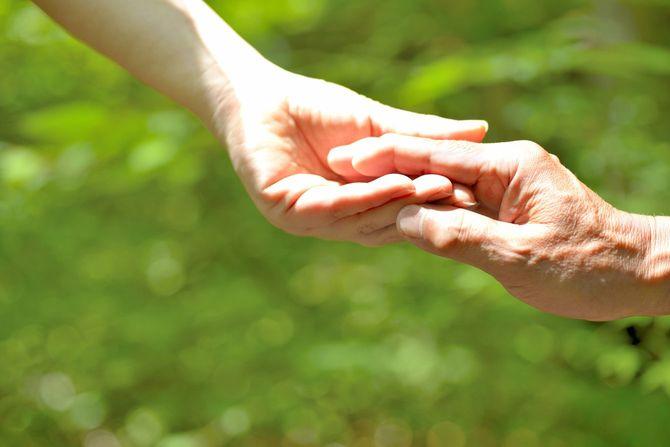 老人の手をとる介護者の手