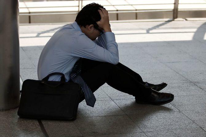 落ち込んで若いアジア ビジネス男の手と感覚の歪み顔を覆っているまたは試みたや失望を強調しました
