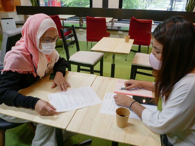 新型コロナウイルスに関する情報について、平易に書かれた資料を使って留学生に説明するインドネシア人スタッフ(左)