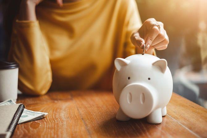 貯金箱にお金を入れる女性の手