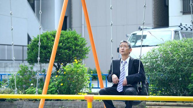 公園でブランコに座る中年男性