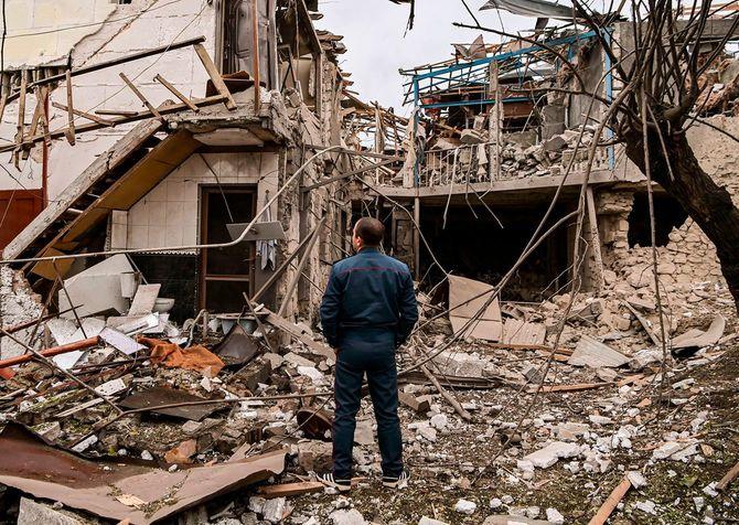 ナゴルノ・カラバフ地域の主要都市ステパナケルトで砲撃を受けた後、破壊された家屋の前に立つ警察官