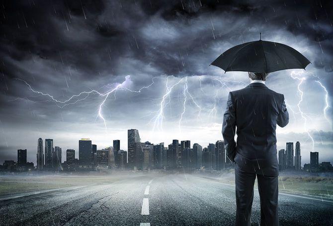 嵐以上の都市を見て傘を持ったビジネスマン