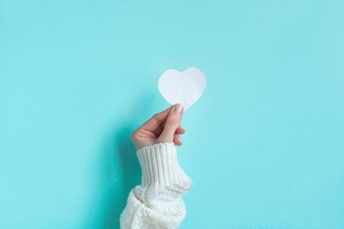 白いハートを持つ女性の手