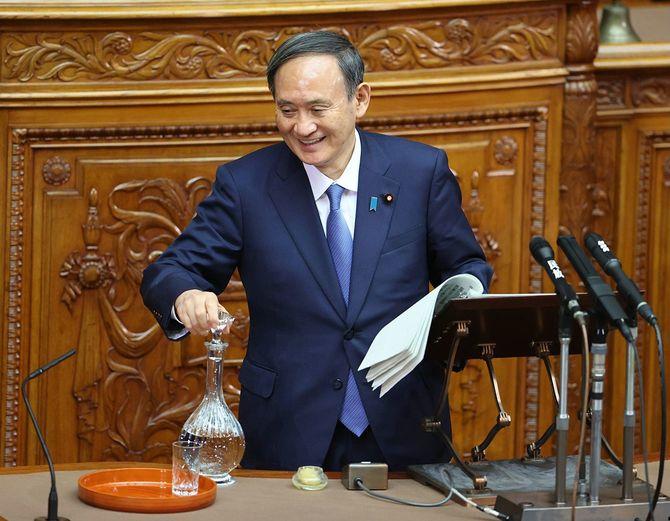 参院本会議での答弁中に、水差しの栓を外さずにグラスに水を注ごうとして苦笑する菅義偉首相