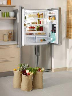 開かれた冷蔵庫のドアといっぱいショッピングバッグ