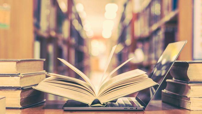 図書館の机の上に、開いて置かれた書籍とノートパソコン