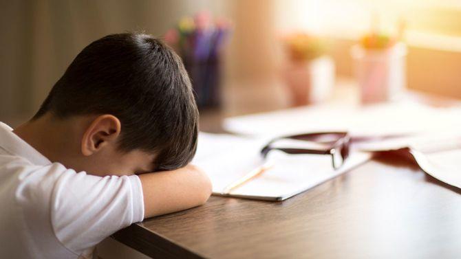 宿題に疲れてテーブルに突っ伏した少年