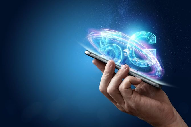 創造的な背景、都市の背景に5Gホログラムを用いた携帯電話を持っている男性の手。5G高速モバイル インターネット、ネットワーク、新世代ネットワークの概念。
