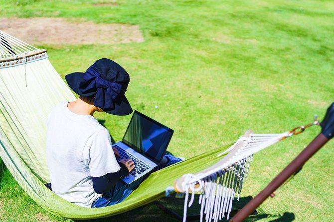 ハンモックの上でノートパソコンの操作