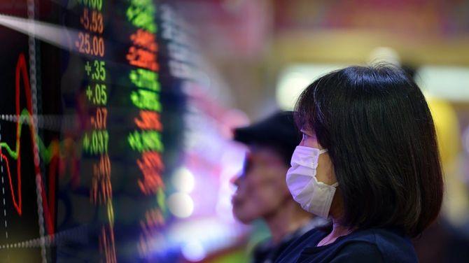 マスクを着けて株価ボードを見つめる女性