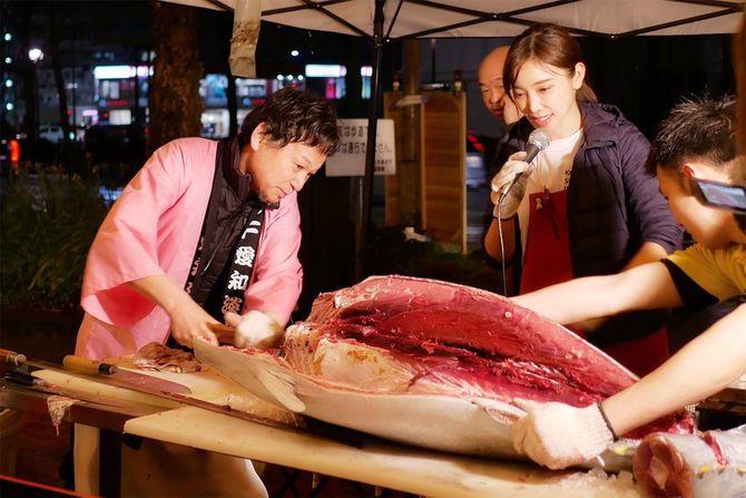マグロの解体ショーを行う森朝奈さん(右)と父・嶢至さん(左)。