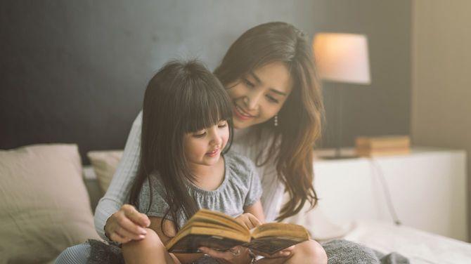 寝室で娘に本を読み聞かせる母親