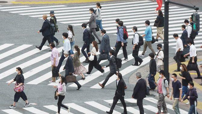 緊急事態宣言解除から一夜明け、東京・渋谷のスクランブル交差点を渡る人たち=2020年5月26日午前
