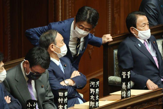衆院本会議場で菅義偉首相(中央左)に声を掛ける安倍晋三前首相(同右)=2021年4月1日、国会内
