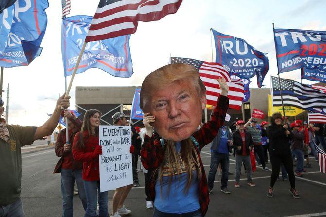 「ストップ・ザ・スティール」の抗議行動に賛同者が集まる中、ドナルド・トランプ米大統領の頭の切り抜きを手にする女性がいる=2020年11月9日、アリゾナ州、フェニックス