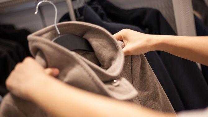 冬物のコートを選ぶ女性の手元