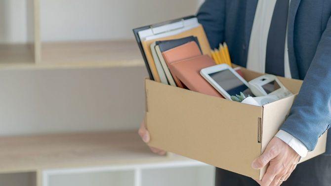仕事を辞めるための箱詰めをするストレスフルなサラリーマン