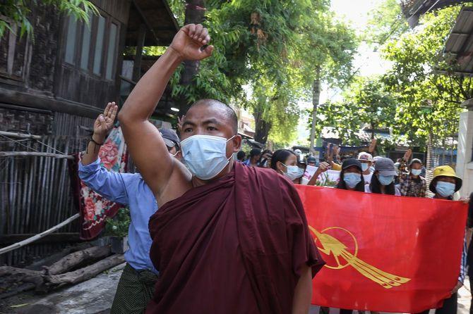 ミャンマー第二の都市マンダレーで、アウン・サン・スー・チー率いる国民民主同盟(NLD)の「戦う孔雀」の旗を掲げ、国軍のクーデターに抗議する人々。三本指のサインは、独裁への抵抗のシンボル。(2021年5月25日)