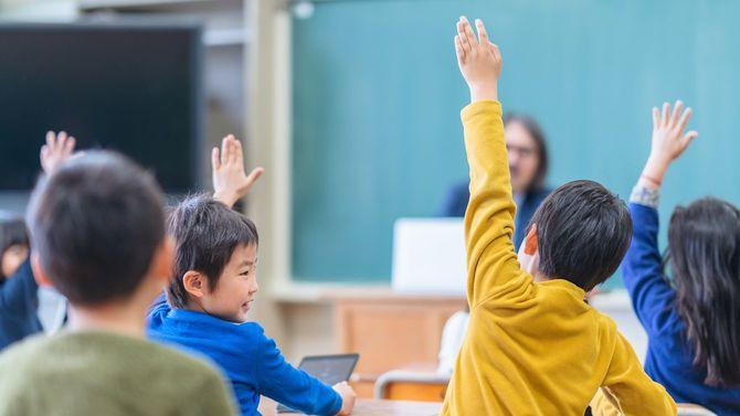 小学校の教室で、一斉に手を挙げる子どもたち