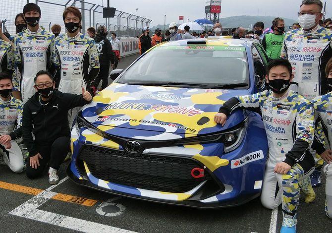 水素エンジン車と写真に納まるトヨタ自動車の豊田章男社長(前列左から2人目)=2021年5月22日、静岡県小山町の富士スピードウェイ