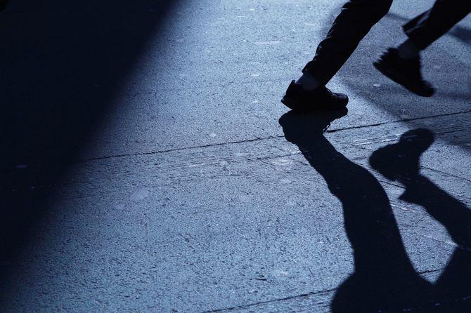 夜中に走り出す男性と影