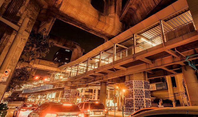 夜間の都市の道路交通と高い橋、都市の構造を過ぎて運転する移動車