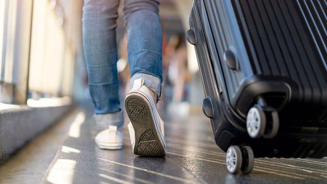 スーツケースをひいて一人で歩く女性旅行者