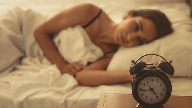 ベッドで横になる若い女性。時計は4時44分を指している。