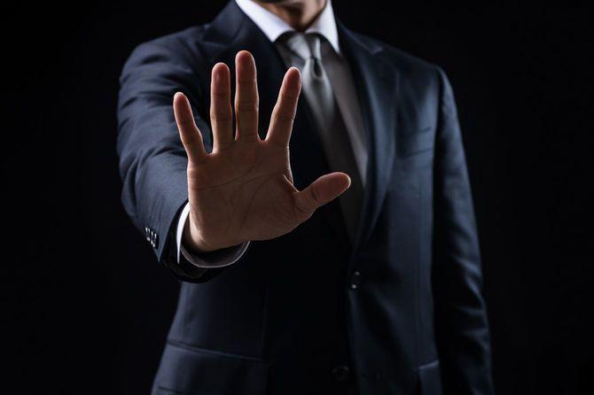 ストップの手振りをするスーツの男性
