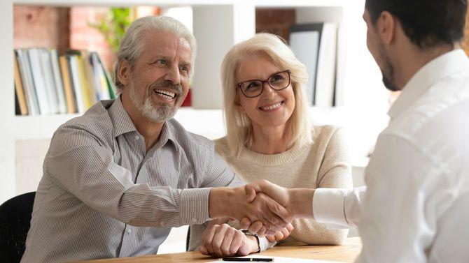 笑顔の老夫婦がエージェントと握手を交わす