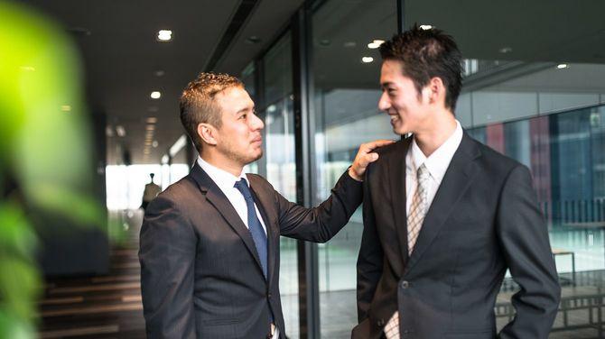 金融街のビルで2人のビジネスマンが立ち話