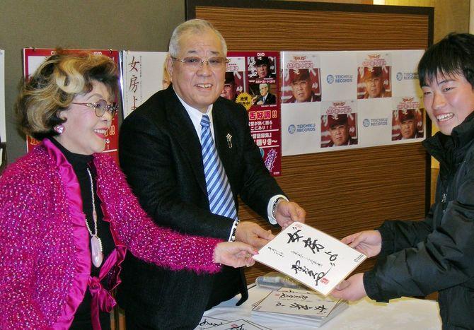 握手会でファンに色紙を渡す楽天の野村克也監督(中央)と沙知代夫人(左)