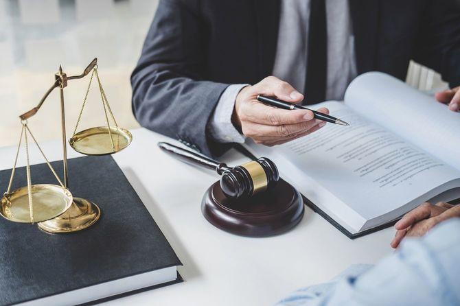 書籍の上に正義のスケールを置き、依頼人と会話する弁護士男性