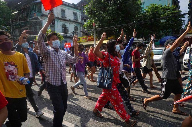 ヤンゴンのダウンタウンで行われた軍事クーデターに反対するデモで、3本指の敬礼をするデモ参加者たち=2021年5月6日