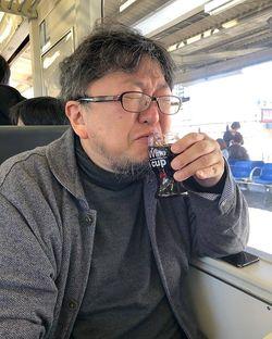 旅先で飲むお酒も大好き。移動中の電車でカップワインをキューっと。