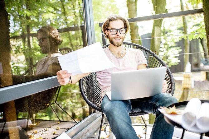 創造的な男が森の家で屋外での作業
