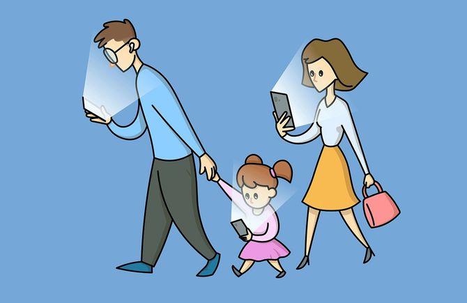 自分の携帯電話を見つめる3人の家族